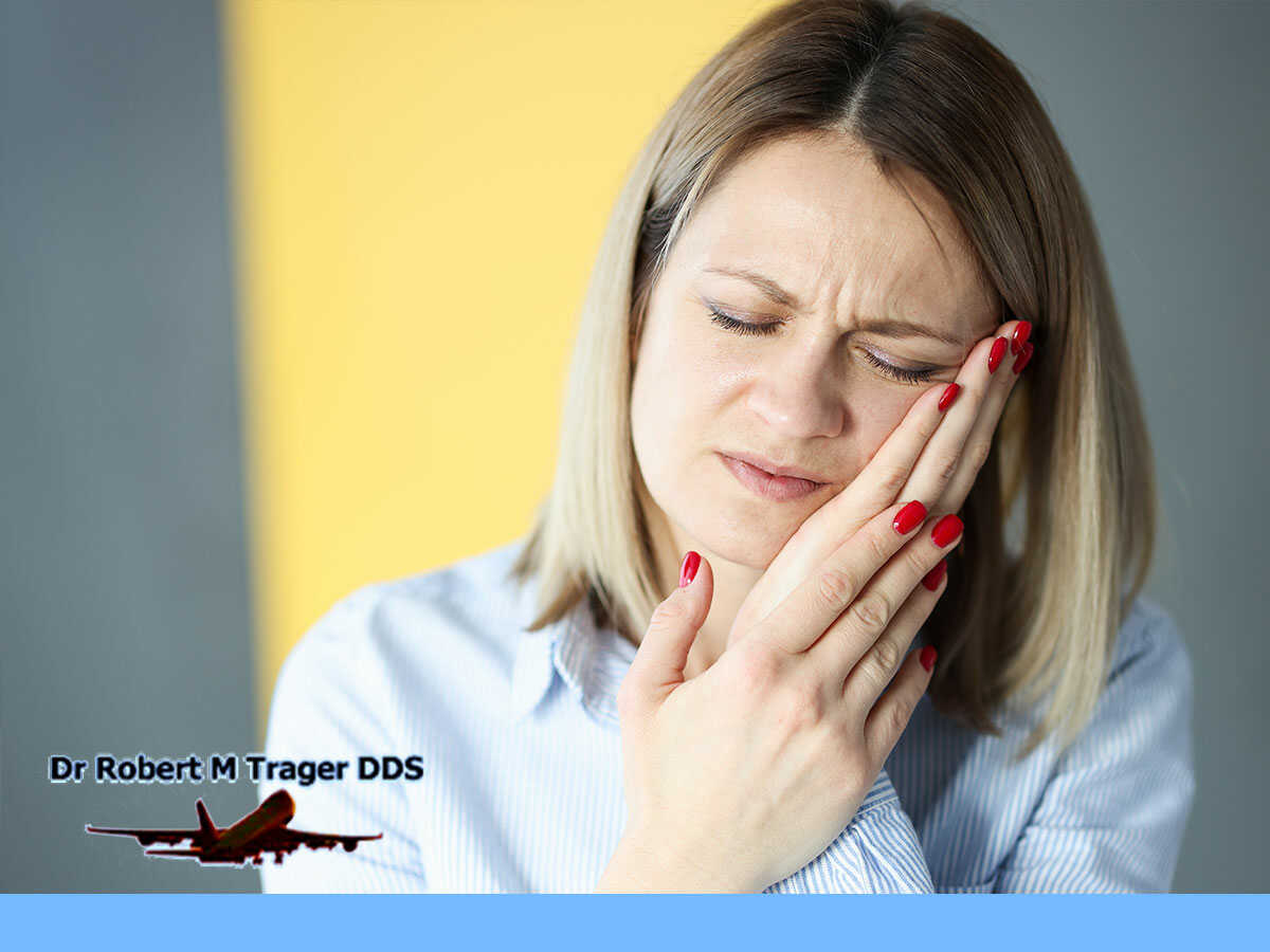A woman with severe tooth pain due to teeth sensibility in Queens, NY.